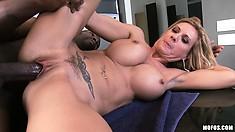 Blonde bimbo with fake tits swallows a big black cock's load