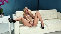 Attractive blonde with perky tits lies on the couch drilling her cunt with a dildo