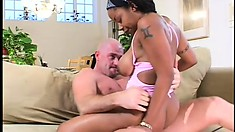Lying on the couch, the busty ebony milf spreads her legs and he drills her holes deep