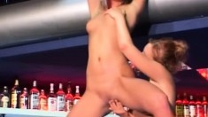 Wild lesbians Elizabeth and Sibylle have fun with a dildo in the bar