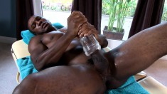 Dark skinned stallion uses his hands and a sex toy to please his cock